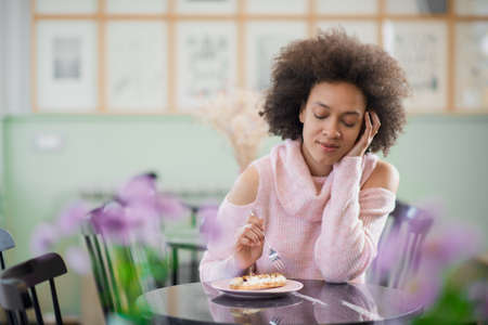 Portrait of charming positive mixed race woman in pink turtleneck sweater sitting in confectionery and eating gateau.