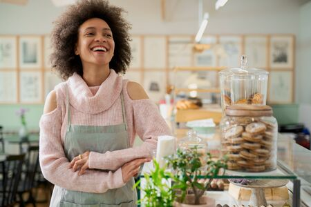 Beautiful smiling mixed race female employee in apron posing in pastry shop next to counter.