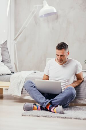 Handsome middle aged man sitting on the floor wirh crossed legs, leaning on bed and using laptop. Foto de archivo - 137895275
