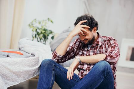 Attractive arab man in jeans and plaid shirt sitting on the floor in bedroom and holding head. Mens issues concept.
