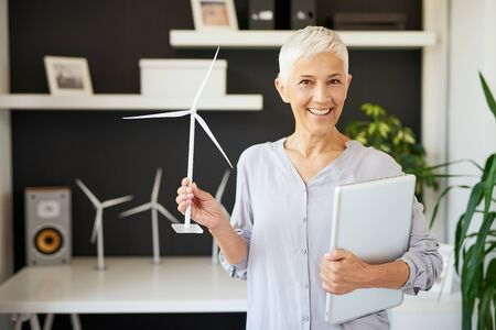 Attractive smiling Caucasian senior woman dressed casual and with short gray hair standing in office, holding laptop and windmill. Sustainable concept.