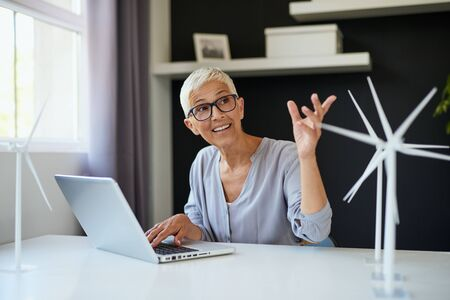 Smiling Caucasian senior woman using laptop and talking to colleague while sitting in office. On desk are laptop and windmill models. Sustainable concept. Stock Photo