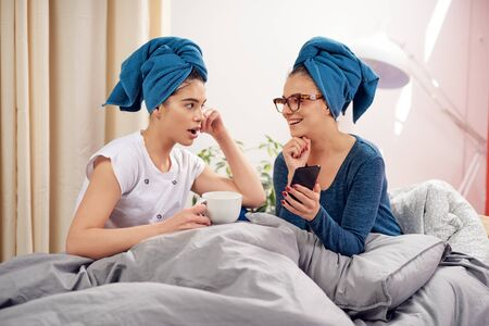Two beautiful Caucasian girlfriends with towels on heads sitting on bed in bedroom, drinking coffee and gossiping.