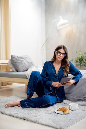 Beautiful Caucasian brunette in blue pajamas and with eyeglasses using tablet while sitting on the floor in bedroom. On floor is breeakfast. Morning time.