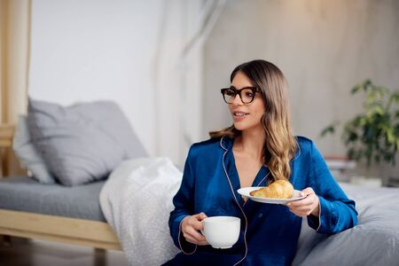 Young Caucasian brunette in pajamas drinking coffee, holding plate with croissant and sitting on the floor in bedroom in morning.