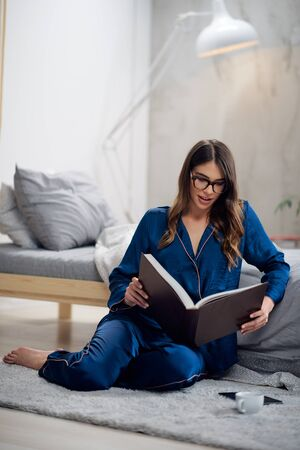 Young gorgeous Caucasian brunette in pajamas sitting on the floor in bedroom and reading book in the morning. Фото со стока