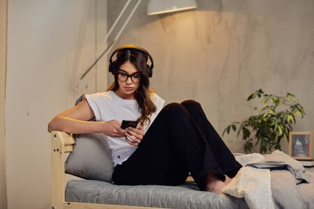 Pretty Caucasian brunette in pajamas and with headphones on head using smart phone late at night while sitting on the bed in bedroom.
