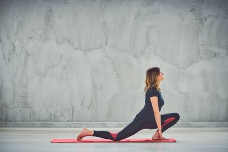 Young slim woman doing lunge on the Knee yoga posture.