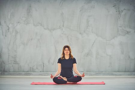 Beutiful woman sitting on the mat in lotus posture.