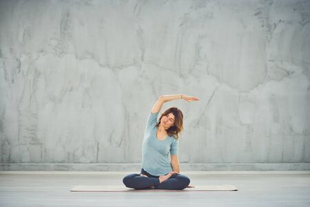 Full length of beautiful Caucasian brunette sitting in lotus position on mat and holding one hand in the air.
