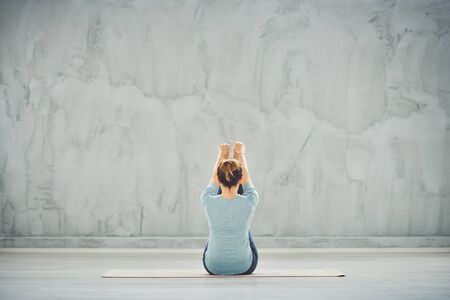 Beautiful Caucasian brunette in blue sportswear sitting on the mat in boat yoga position with backs turned. Stock Photo