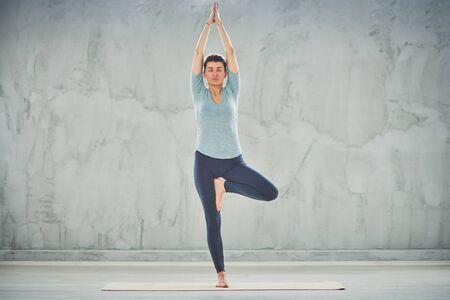 Full length of beautiful Caucasian brunette doing Tree yoga pose on mat barefoot.