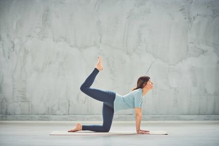 Beautiful Caucasian brunette in blue outfit doing One Legged Boxyoga pose on mat. Фото со стока