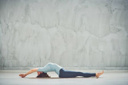 Full length of beautiful Caucasian brunette lying down on mat with hands outstretched and doing fish yoga exercise.
