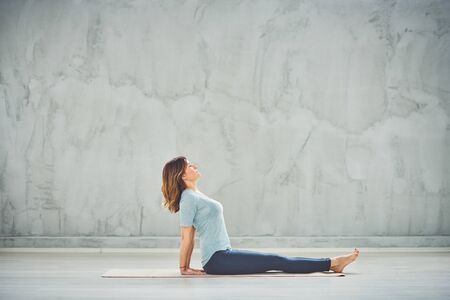 Side view of charming Caucasian brunette sitting on the mat and doing yoga exercises.