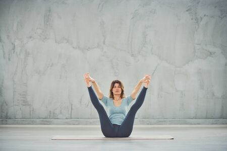 Charming Caucasian fit brunette sitting in boat yoga pose.