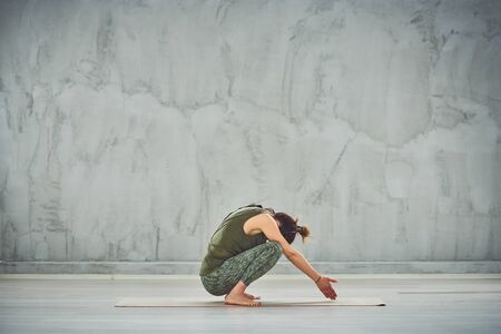 Young Caucasian woman squatting on mat and doing Garland yoga posture.