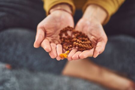 Close up of woman holding Tibetan prayer beads.