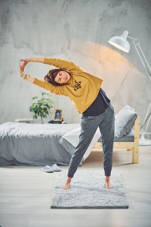 Full length of gorgeous fit brunette stretching on rug in the morning. Yoga practicing concept.