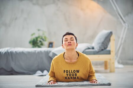 Beautiful Caucasian brunette doing Low Cobra yoga pose while lying on stomach in bedroom in morning.