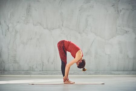Side view of beautiful Caucasian brunette in red sports wear standing barefoot on the mat in Standing Forward Bend yoga posture. Фото со стока
