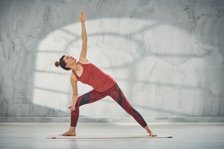 Beautiful Caucasian brunette doing Revolved Warrior with Arms Extendedyoga pose on mat barefoot. Фото со стока