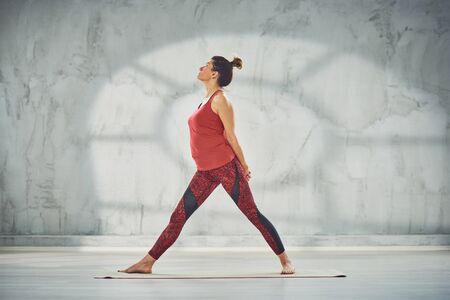 Beautiful Caucasian brunette in red sportswear doing Star with Hands Interlaced yoga pose on mat barefoot.