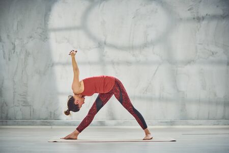 Attractive brunette in red sportswear barefoot doing Triangle yoga posture. Фото со стока