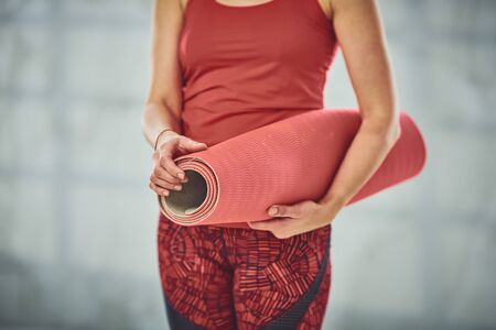 beautiful Caucasian woman dressed in red outfit holding exercise mat. Yoga exercise concept.