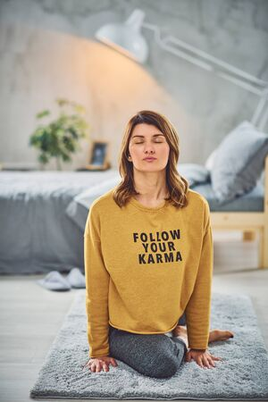 Beautiful Caucasian brunette sitting on the mat in bedroom in One Legged King Pigeon yoga pose.