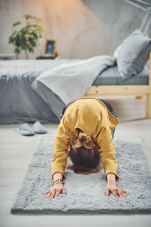 Brunette doing Extended Child's yoga posture on the rug in bedroom.