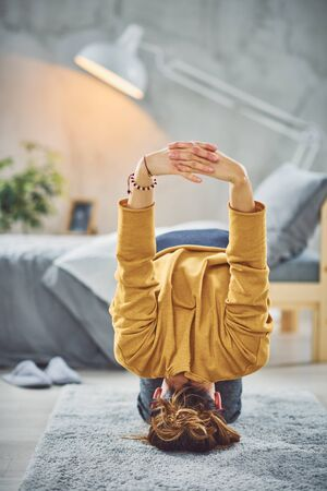 Beautiful Caucasian brunette doing Headstand yoga pose in bedroom on rug. Фото со стока