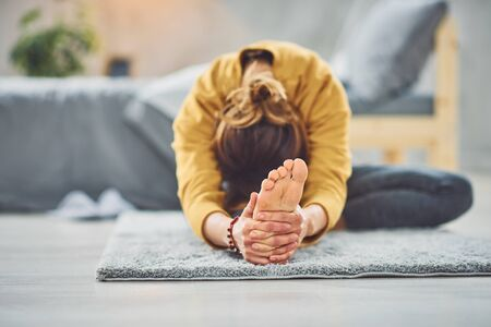 Caucasian brunette stretching leg while sitting on the rug in bedroom.