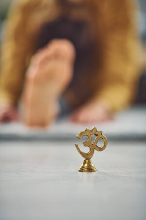 Close up of om sign. In background woman exercising yoga. Selective focus on om.