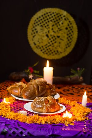 pan de muerto, placed on white plates, adorned with cempasuchil petals and burning candles around it. Diffuse background with confetti, traditional Mexican Foto de archivo