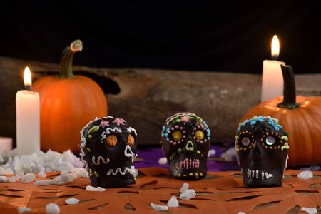 Hand-made skulls, main ingredients melted chocolate and colored icing sugar, placed on confetti. In the background pumpkins, candles and a wood. Day of the dead Mexican tradition Foto de archivo