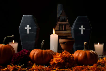 Pumpkins surrounded by marigold flower, lighted candles and two cardboard coffins and a copal, in the background in diffuse a house made of cardboard.
