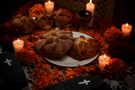 Traditional and sugary bread of the dead, around it marigold flowers, cardboard coffin, lighted candles, diffused confetti background.