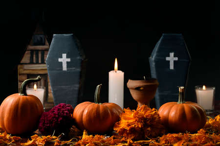 Three pumpkins surrounded with marigold flower, lighted candles and two vertically cardboard coffins and a copal, in the background in diffuse a house made of cardboard.