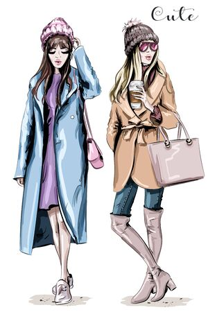 Two fashion women. Hand drawn stylish beautiful women in winter clothes. Fashion winter outfits. Sketch. Ilustração