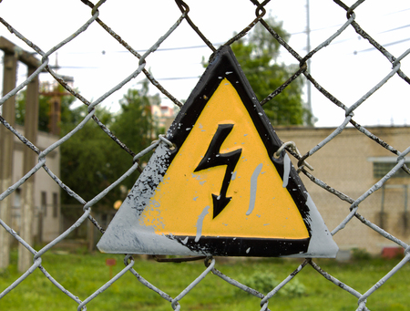 high-voltage wires, a sign on the fence the danger Stock Photo