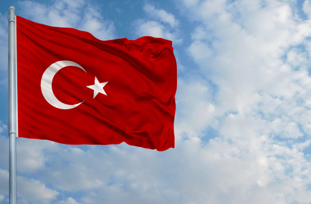 National flag of Turkey on a flagpole in front of blue sky.