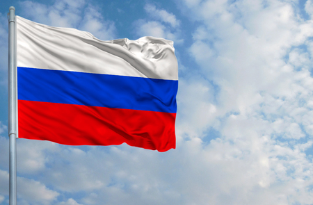 National flag of Russia on a flagpole in front of blue sky.