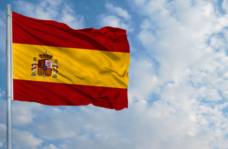 National flag of Spain on a flagpole in front of blue sky.