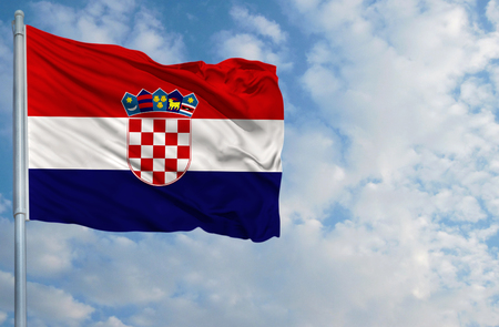 bandera croacia: National flag of Croatia on a flagpole in front of blue sky.