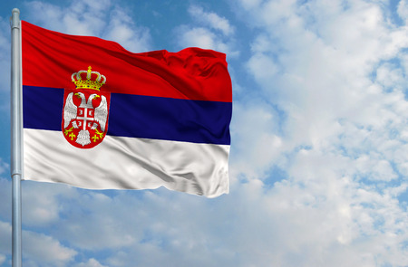 National flag of Serbia on a flagpole in front of blue sky. Stock Photo