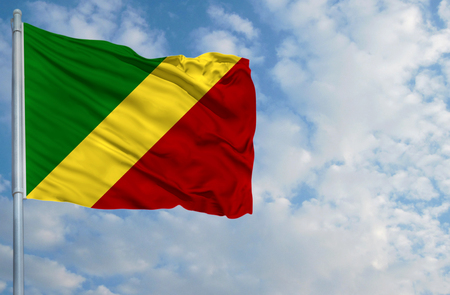 National flag of Congo,Republic on a flagpole in front of blue sky.