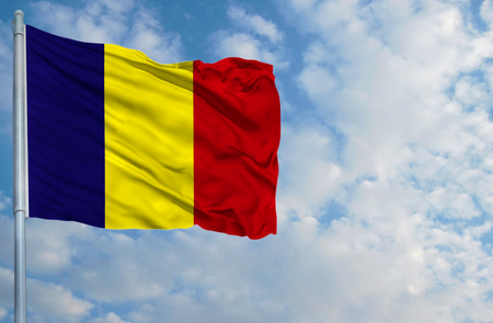 National flag of Romania on a flagpole in front of blue sky.