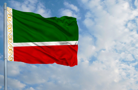 on top of the world: National flag of Chechen Republic on a flagpole in front of blue sky.