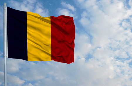 chad: National flag of Chad on a flagpole in front of blue sky.
